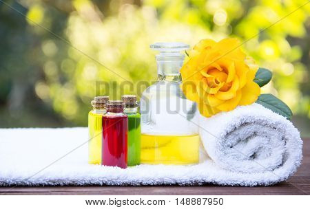 Closeup of bottle with rose essential oil and floral elixirs for beauty. White terry towel soft and fragrant yellow rose. Cosmetics for saunas and spa treatments. Spa concept. Copy space.