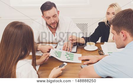 Business meeting. Young happy businessmen and women at modern office, team corporate discussion at workplace, show information on tablet. Brainstorming and communication with partners for startup