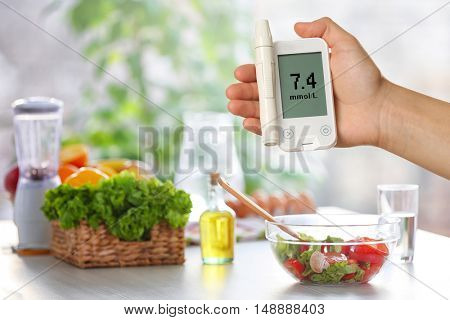 Male hand holding glucometer with products on table in the kitchen. Diabetes concept