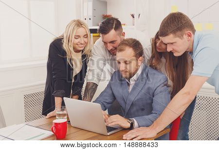 Business people group portrait look attentive at laptop in the office. Successful corporate team of female and male coworkers check internet site of company together, partners and colleagues.