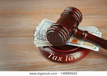 Law gavel with dollars on wooden table background, closeup. Tax law concept