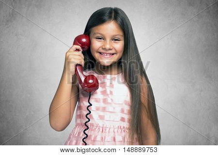 Smiling little girl talking on a vintage telephone. Grey grunge background
