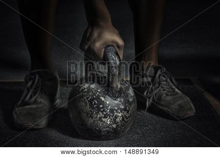 Sport. Unrecognizable strong athlete is going to do exercise with weight -- selective focus toned and stylized photo