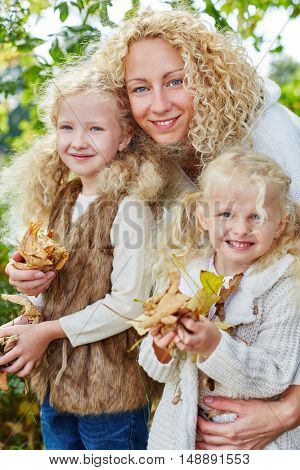 Portrait of mother and daugthers in autumn at the park