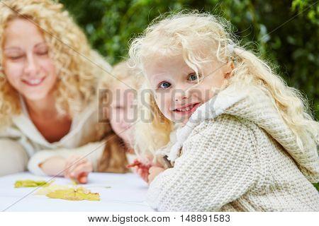 Little girl in kindergarten drawing and having fun
