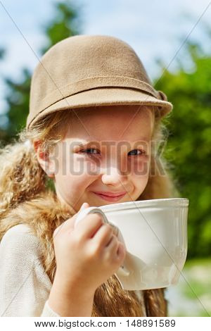 Portrait of blond girl with cup in autumn in garden