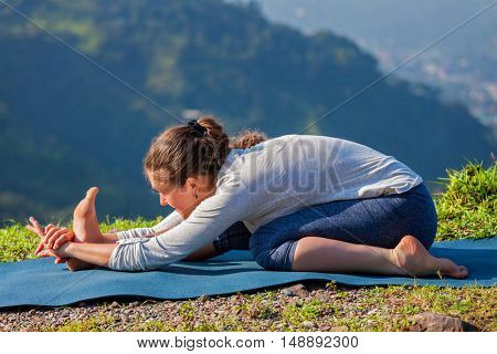 Yoga outdoors - woman doing Ashtanga Vinyasa yoga Tiryam-Mukha Eka-Pada Paschimottanasana asana stretching position outdoors