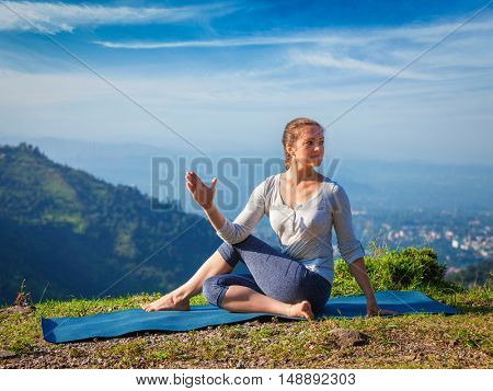 Yoga exercise outdoors -  woman doing Ardha matsyendrasana asana - half spinal twist pose mountains in Himalayas in India in the morning
