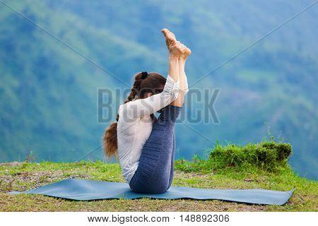 Yoga - sporty fit woman practices Ashtanga Vinyasa yoga asana Urdhva mukha paschimottanasana - upward facing intense west stretch oudoors