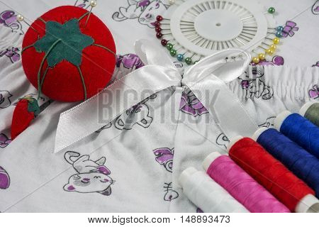 Several sewing tools are on the textile