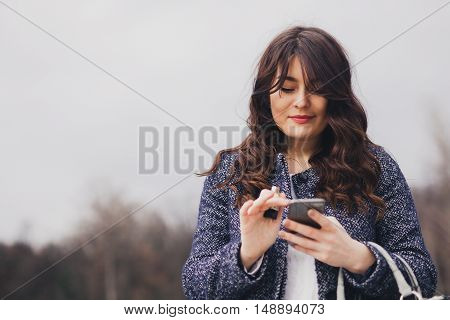 SMS. Closeup portrait young girl looking at phone and messaging with copy space