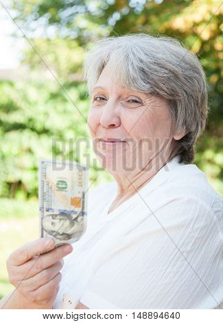 Old age woman holding US dollars