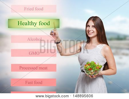 Choose healthy food and diet concept. Young smiling woman outdoors holding fresh vegetable salad meal and touch big transparent futuristic screen, push button. Modern dieting and weight loss nutrition