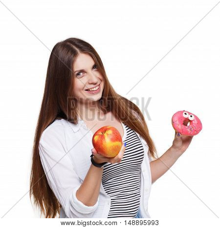 Choose healthy food, diet concept. Beautiful long-haired young woman with big ripe red apple in one hand and a donut in another. Female portrait isolated on white background.