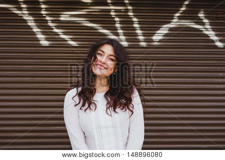Woman smiling with perfect smile and white teeth over urban wall with grafitti. Plus size model