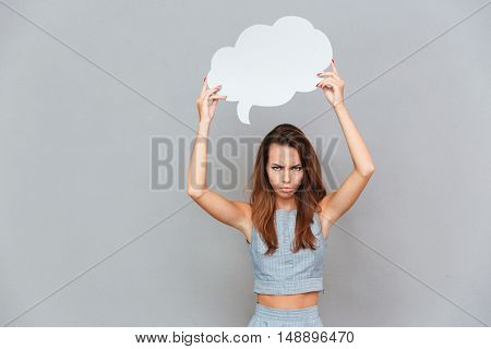 Sad frowning young woman standing and holding empty speech bubble over grey background