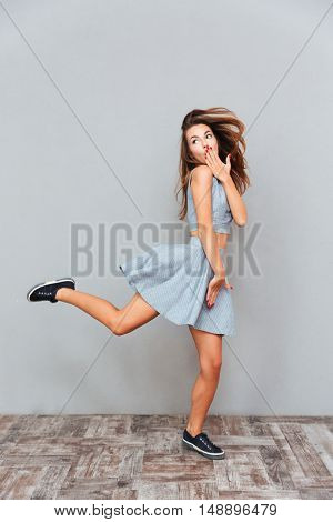 Amazed carefree young woman running over grey background