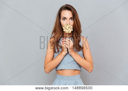 Funny cute young woman covered her mouth with lollipop over grey background