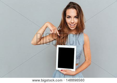 Cheerful cute young woman holding and pointing on blank screen tablet over grey background