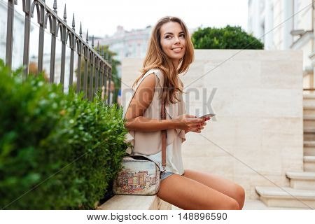 Smiling cheerful young woman resting and holding mobile phone outdoors