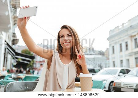 Happy smiling beautiful girl making selfie and showing victory sign while sitting in cafe outdoors