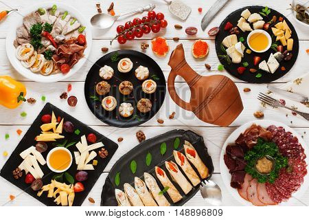 Tasty snacks variety with clay jug, flat lay. Appetizing cheese, meat meals, pancakes and canape with red caviar. Russian tableful with wine concept