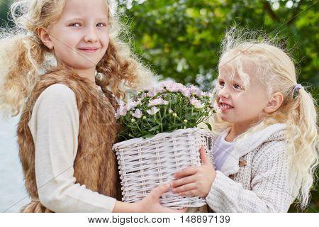 Two girls with flower basket during gardening in autumn