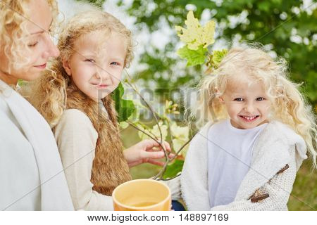 Family with two sibling girls in garden in autumn