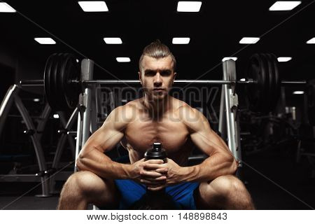 Portrait muscular man workout with barbell at gym. Muscular guy sitting with a bottle of water in the gym. Bodybuilder man with a shaker. Bodybuilder Resting After Exercise And Hold From Shaker