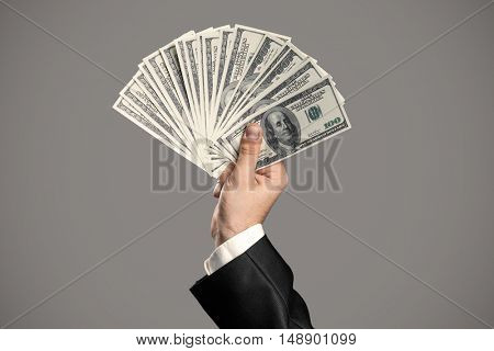 Business Man's Hand To Holding Money. Handful Of Dollars On Gray Background.