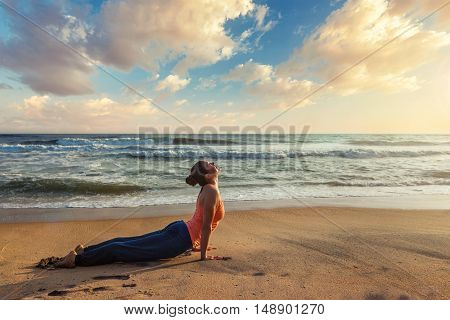 Yoga outdoors on beach - woman practices Ashtanga Vinyasa yoga Surya Namaskar Sun Salutation asana Urdhva Mukha Svanasana - upward facing dog pose on sunset. Kerala, India
