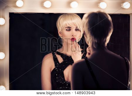Beautiful Blonde Woman Looking Into The Mirror At Herself And Applying Red Lipstick.