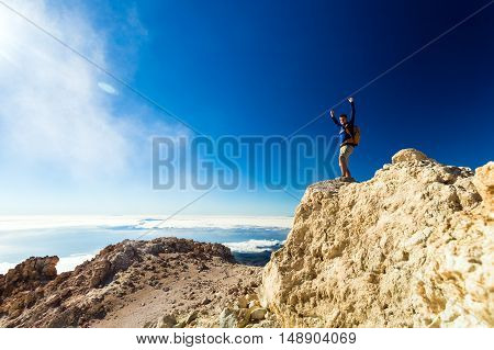 Man tourist hiker climber or trail runner looking at beautiful inspirational landscape in mountains. Fit runner with arms up outstretched happiness freedom and inspiring view on rocks top Tenerife.