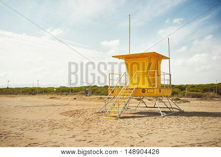 Footprints on an empty beach around a bright yellow lifeguard post Commercial image