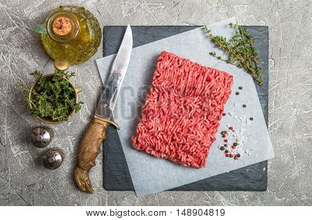 Minced meat on paper and slate with seasoning and fresh thyme on gray background, top view