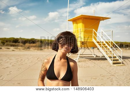 Young beautiful woman with bob haircut wearing black bikini smiles into the camera on an empty beach with a yellow lifeguard post in the background