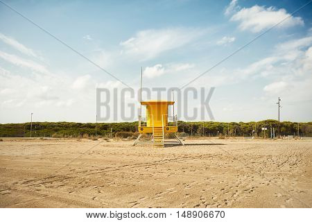 Sand around a yellow lifeguard tower on an empty beach covered with footprints and tracks on a clear day