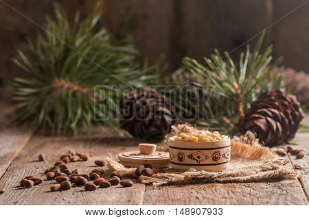 Cedar nuts and branch with cone on wooden background