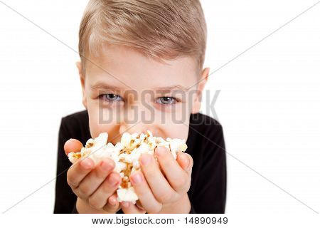 The boy eats popcorn
