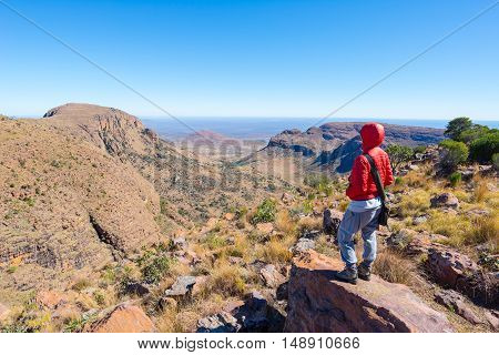 Tourist standing on rock and looking at the panoramic view in Marakele National Park one of the travel destination in South Africa. Concept of adventure and traveling people.