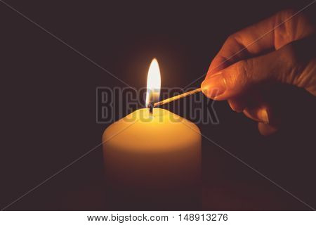 Vintage tone of hand with matchstick lighting a candle