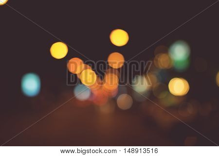 Vintage tone of Bright circles from streetlamps on defocused photo of night street.
