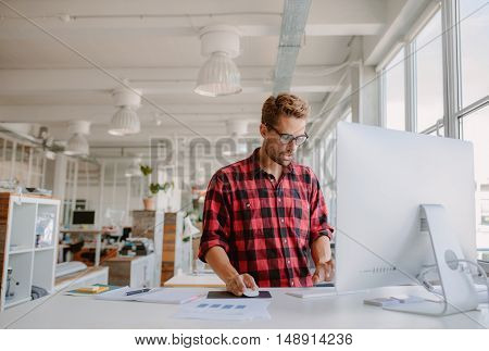 Young Man Working On Computer In Modern Office