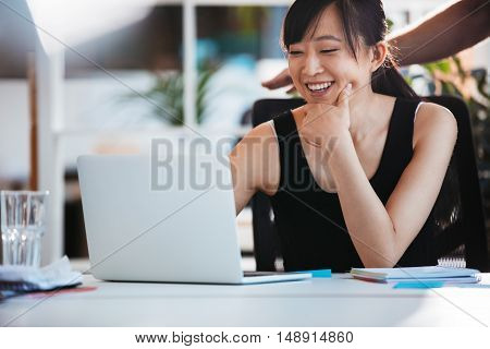 Shot of young smiling woman sitting at her desk and working on laptop. Asian female executive using laptop computer.