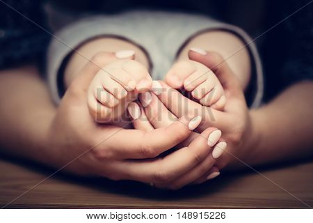 Little baby feet in mother's hands. Concept of child care, feeling safe, protect.