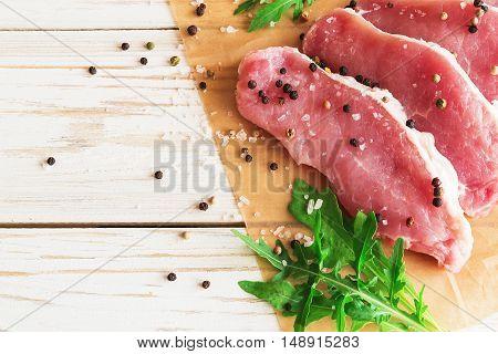 Fresh Raw Pork Meat With Salt, Pepper And Arugula.