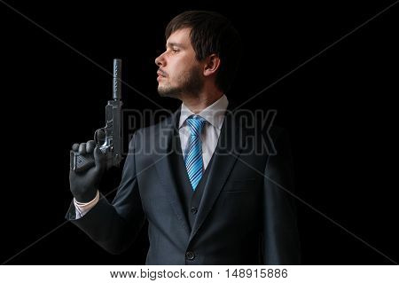 Spy Or Agent Holds Pistol With Silencer In Hand On Black Backgro