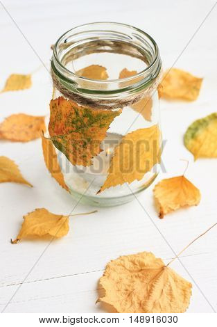 Fall craft. Tea light candle in glass jar, decorated dry autumn leaves. Simple cute household DIY decor. Soft light and focus.