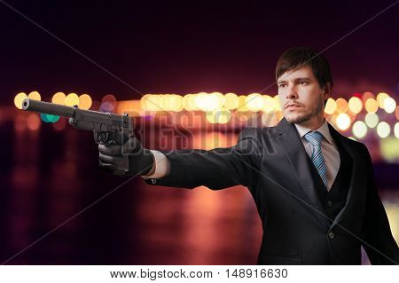 Hitman Or Secret Agent Is Aiming With Pistol At Night.