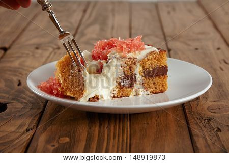 Close up shot of a beautiful vintage fork and a slice of a moist light brown sponge cake with grapefruit and cream